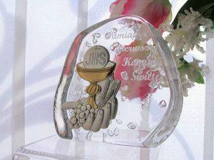 """Pamiątka w formie posrebrzanego obrazka umieszczonego na podstawie ze szkła kryształowego. Na szkle wygrawerowano napis """"Pamiątka Pierwszej Komunii Świętej"""""""