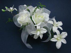 Kompozycja ze sztucznych kwiatów w szklanym naczyniu
